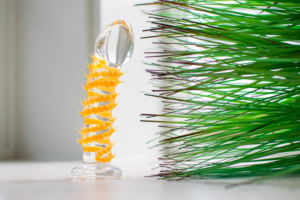 The Taffy Tickler Silicone Sweets glass dildo, covered in little orange spikes, standing upright near some pointy green fake grass.