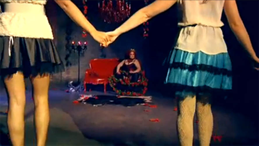 Two women holding hands in front of the Queen of Hearts, April Flores, sitting on her throne.