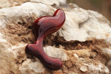NobEssence Romp anal plug, lying on a craggy rock in the great outdoors.