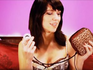 A lingerie-clad woman holding the Rock 'n' Roll Massager, a leopard-print vibrating make-up case. Essentially.