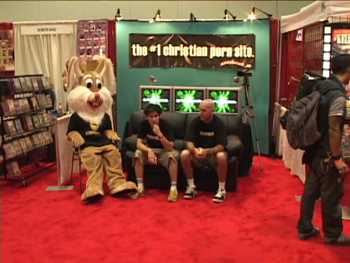 Craig and Mike's booth at a porn convention, where they sit alone with their rabbit friend.