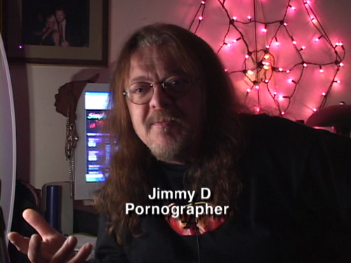 JIMMY D. PORNOGRAPHER. In front of a set of pink twinkle lights shaped like a cobweb.