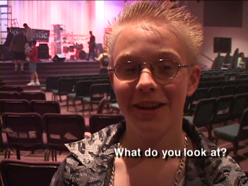 "A kid with bleach-blonde spiky hair and a smirk on his face, answering the question ""what do you look at?"""