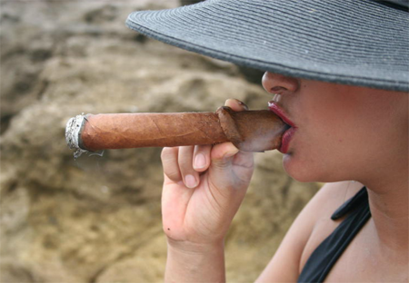 A woman smoking an enormous cigar that is shaped like a penis. It looks ridiculous.