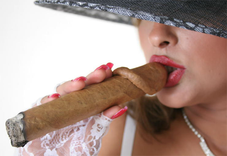 A woman smoking an enormous cigar that is shaped like a penis.