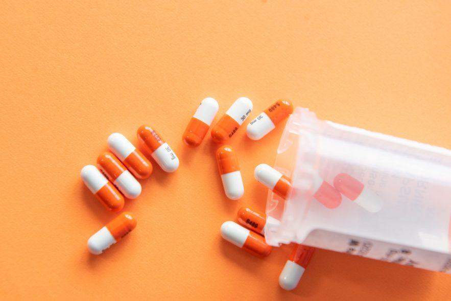 Pills spilled on an orange surface.