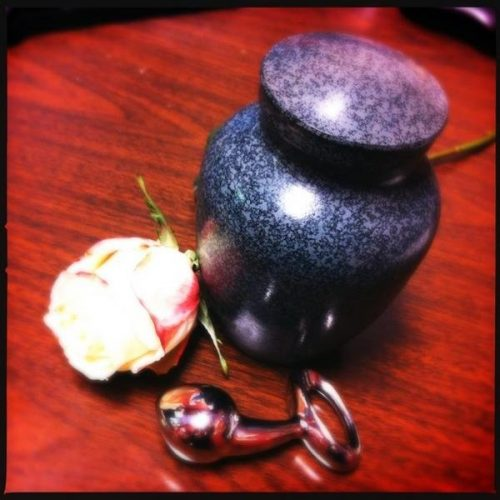 A fancy urn on a wooden table, with the Pure Plug and a rose next to it.