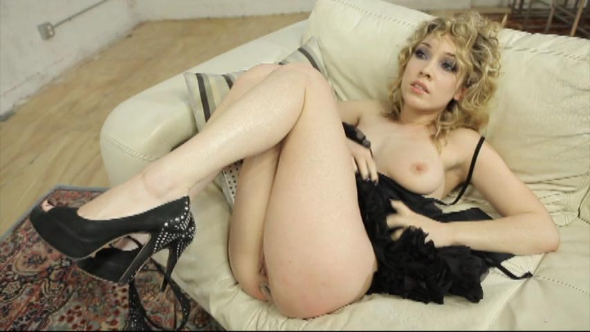 Lily LaBeau looking sexy with her skirt pulled up, sitting on a couch.