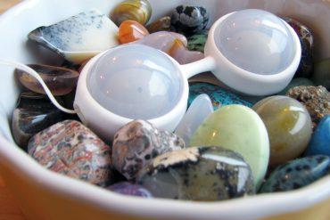 LELO Luna Beads Mini lying in a dish full of colorful stones.