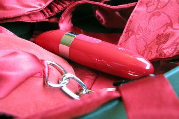 LELO Mia 2 in the Adore Me Pleasure Set, lots of red satin-y stuff surrounding the vibrator.