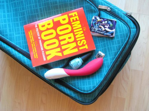The Feminist Porn Book lying on top of my suitcase, with the LELO Mona 2 and some business cards.
