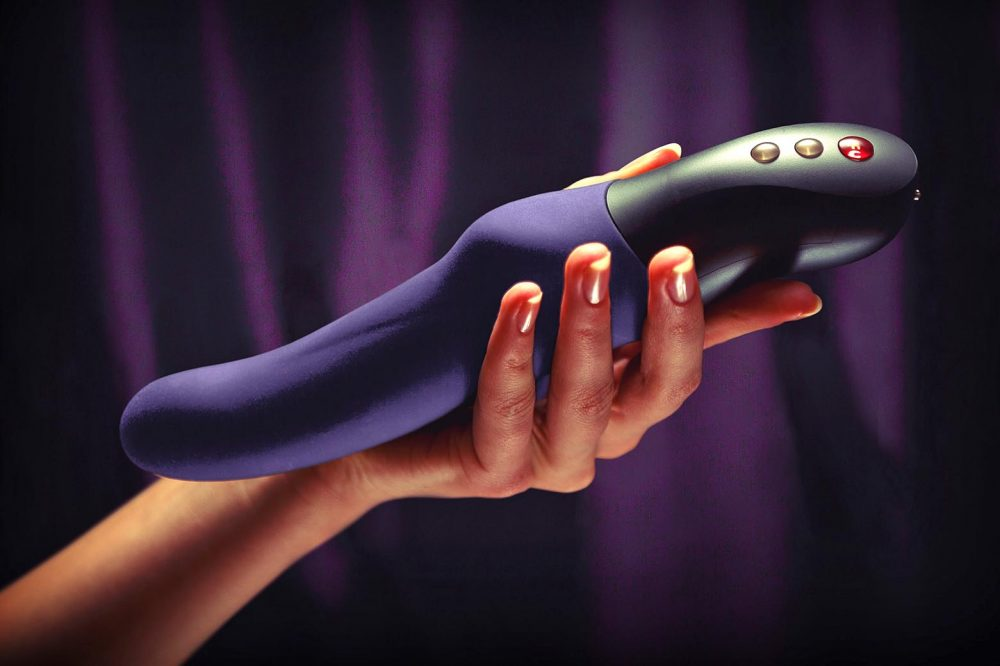 Person holding the Fun Factory Stronic Eins in front of a curtain.