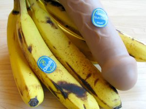 Vixen Creations Buck dildo with a bunch of bananas. Accordingly, the dildo has a Chiquita sticker on it that says NATURAL NUTRITION.