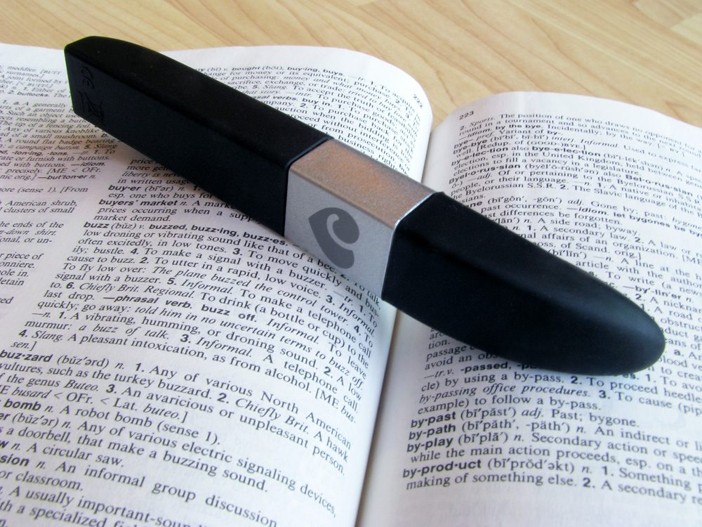 "Lovehoney Flash USB rechargeable vibrator on top of a dictionary, open to the definition of ""buzzy."""