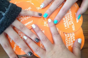 Lorax, me, and Queerie Bradshaw showing off our special conference manicures on top of some Tantus stickers.