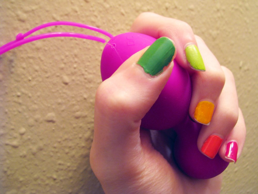 Me grasping the Jopen VR1 kegel balls, with rainbow-painted nails.