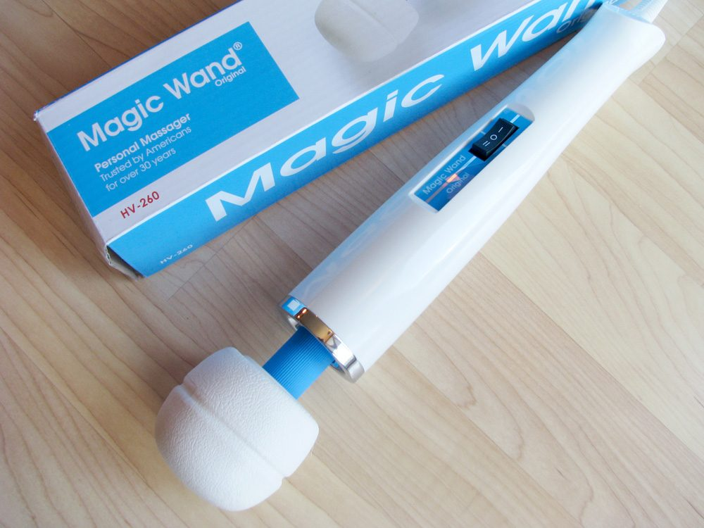 Hitachi Magic Wand Original and its box, on a hardwood floor.