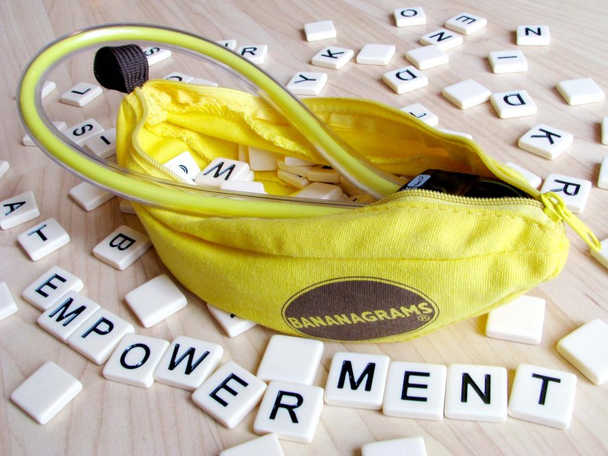 "Magic Banana kegel exerciser and dildo, surrounded by plastic letters from the Bananagrams game spelling out ""EMPOWERMENT."""