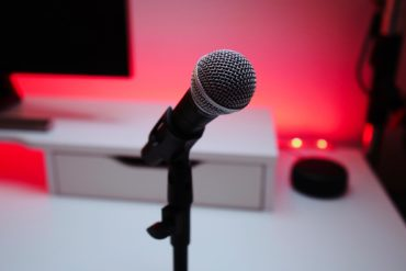 Microphone in front of a computer, with some pretty red lighting in the back.