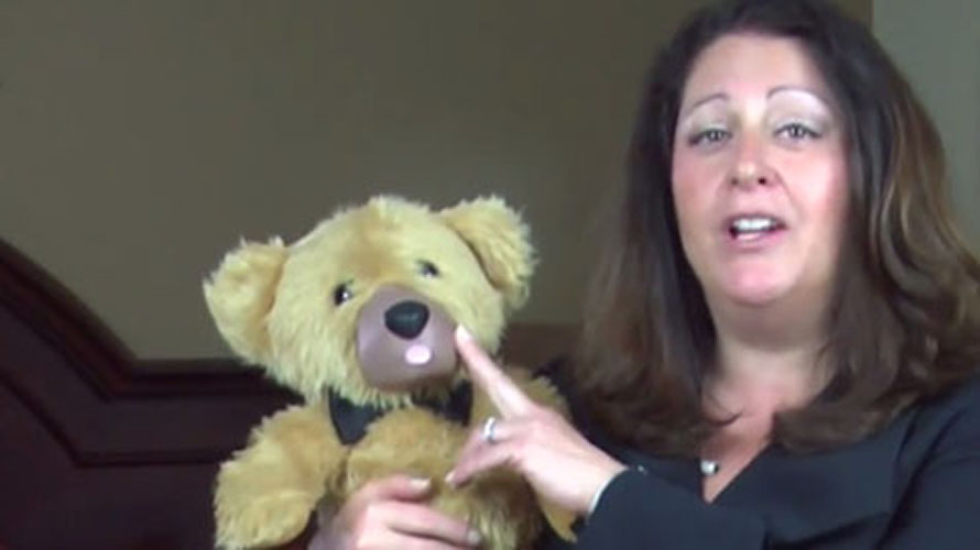 Screenshot from the now-defunct Teddy Love crowdfunding video, of a woman touching a teddy bear's nose.