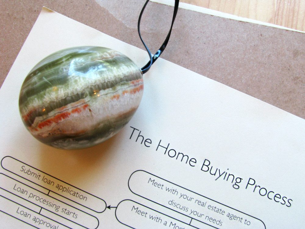 """Stone egg lying on top of a brochure for """"the home buying process."""""""