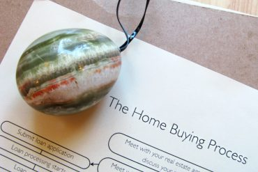 "Stone egg lying on top of a brochure for ""the home buying process."""