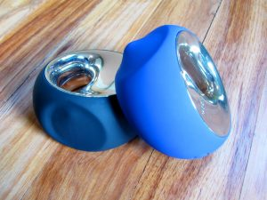 Black LELO Ora (original), blue LELO Ora 2 on a hardwood floor.