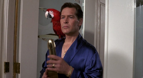 Hugo Posh (James Remar) being majestic in The Girl Next Door, holding a porn trophy, with a Macaw perched on his shoulder.