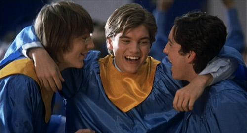Klitzy (Paul Dano), Matthew (Emile Hirsch), and Eli (Chris Marquette) hugging in their graduation gowns in The Girl Next Door.