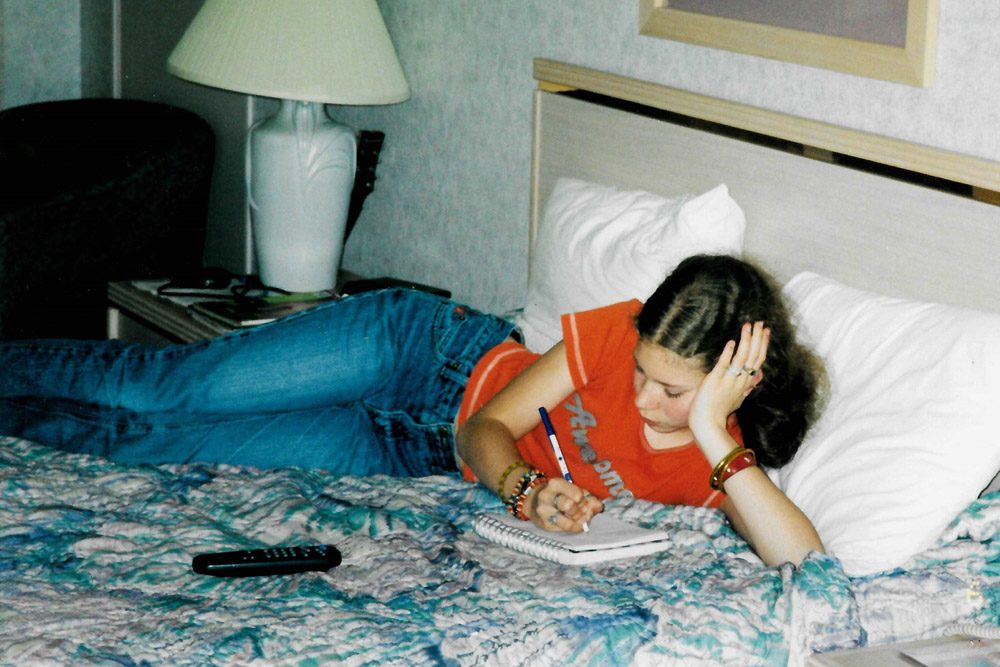Me in a motel in 2002, on the bed writing in my journal.