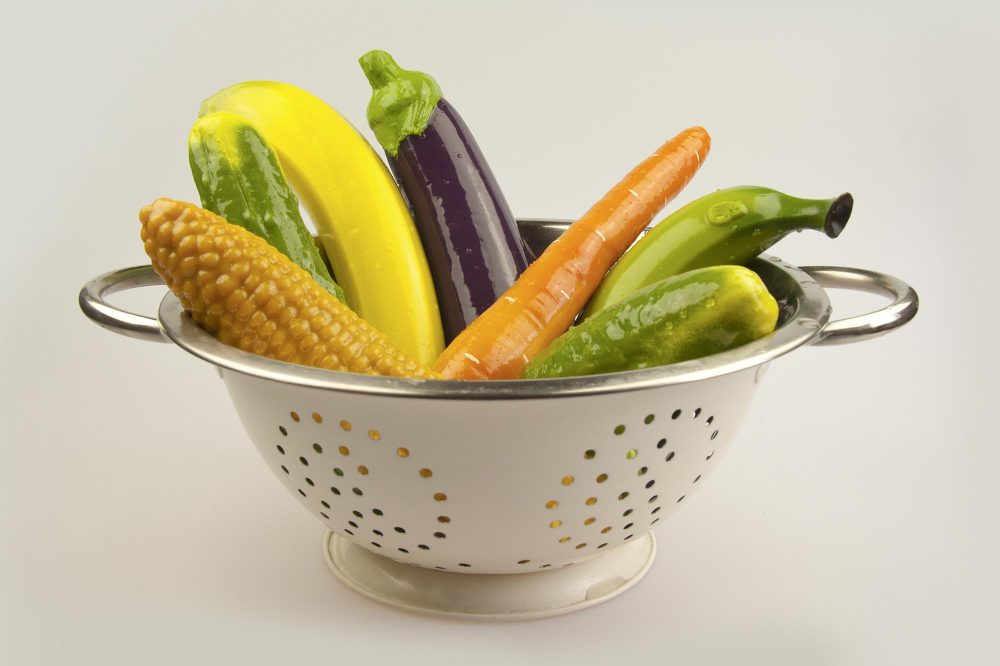 A literal colander full of silicone sex toys shaped like various vegetables and fruit: corn, carrot, eggplant, banana...