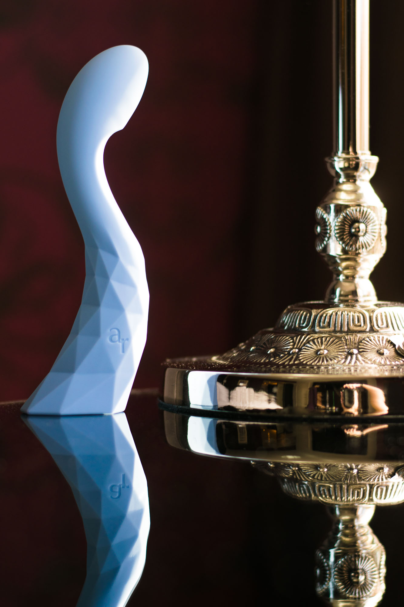 L'Amourose Prism V rechargeable G-spot vibrator standing up on a reflective table, next to an ornate golden lamp.