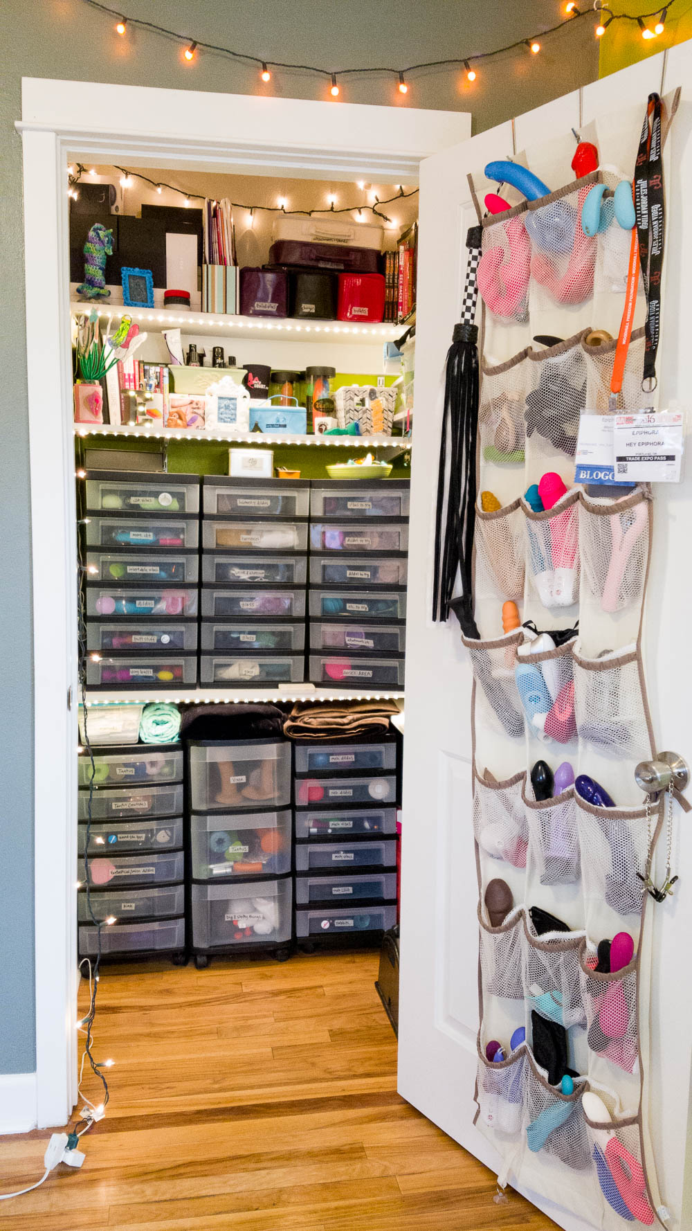 IS IT NOT GLORIOUS, THIS SEX TOY CLOSET. Pretty lights, over-the-door dildo organizer, tons of plastic drawers.