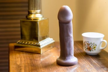 New York Toy Collective Carter silicone dildo on a nightstand, next to a golden lamp base and a floral tea cup.