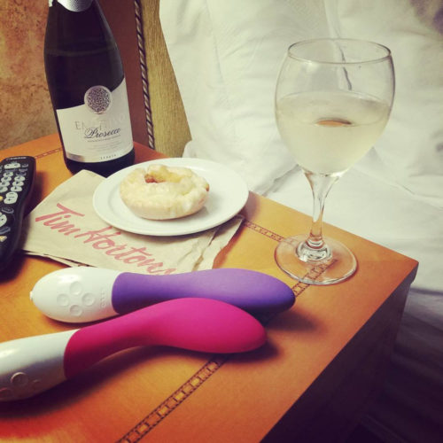 Two LELO Mona 2s on my nightstand with wine and donut.