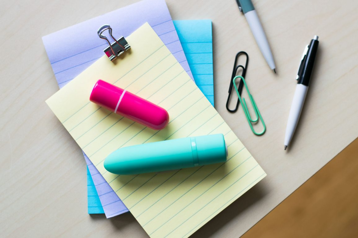 Screaming O Charged Vooom and Positive rechargeable bullet vibrators on top of a pile of colorful lined notepads.