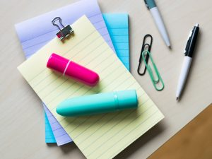 Screaming O Charged Positive and Vooom rechargeable bullet vibrators on top of a pile of colorful lined notepads.