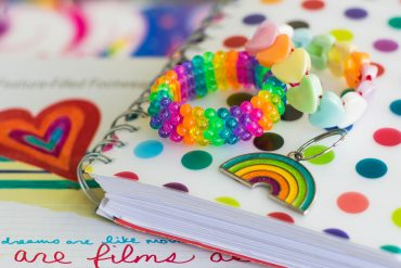 Rainbow notebook, bracelets, and keychain.
