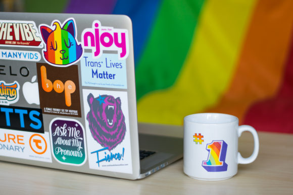 """Aerie's laptop, plastered with awesome stickers including one which reads """"Ask Me About My Pronouns"""""""