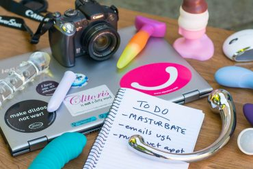 Sex toy reviewer spread: camera, laptop, to-do list, and sex toys everywhere.
