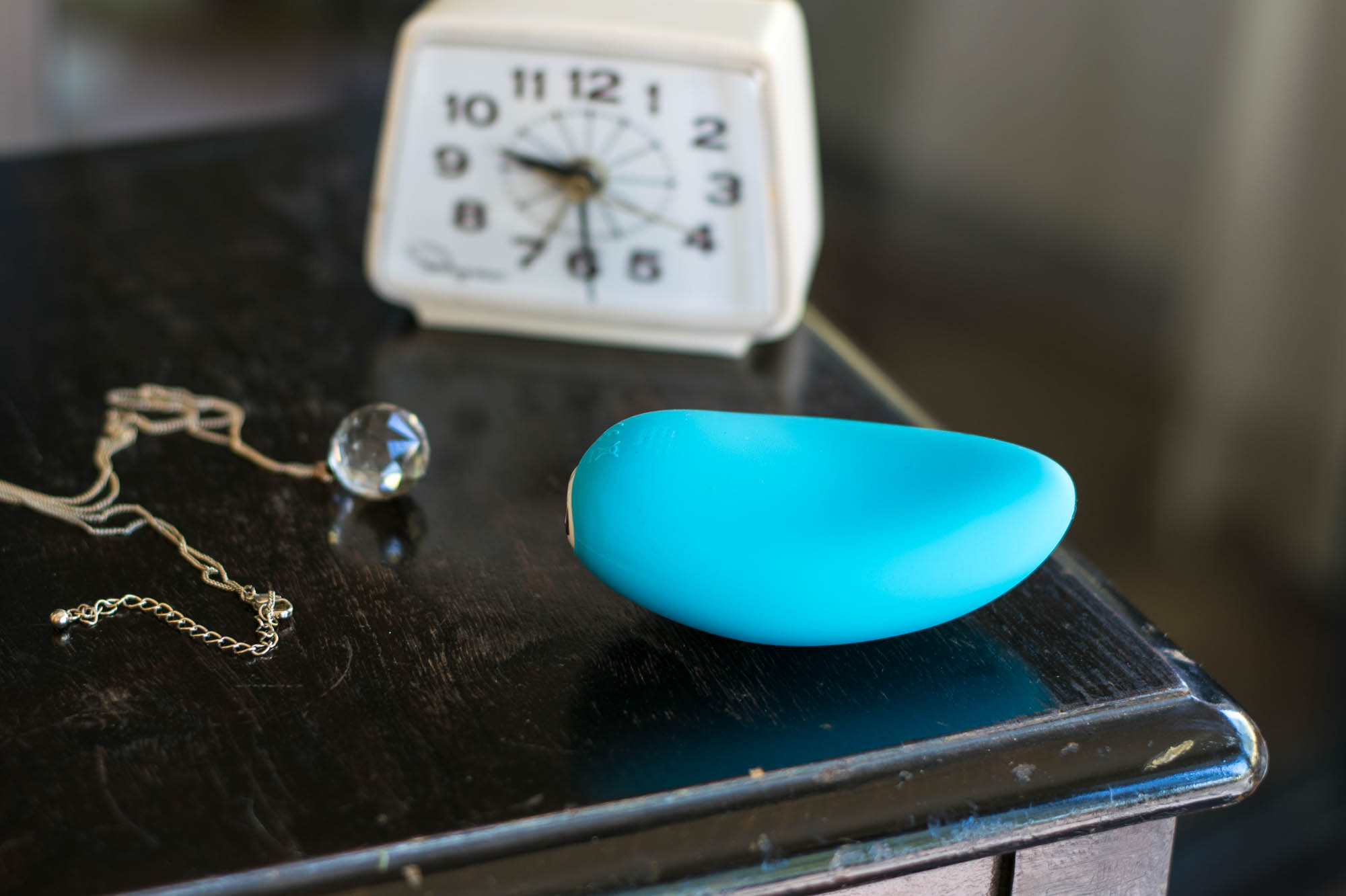We-Vibe Wish rechargeable clitoral vibrator lying on a clear glass sculpture.