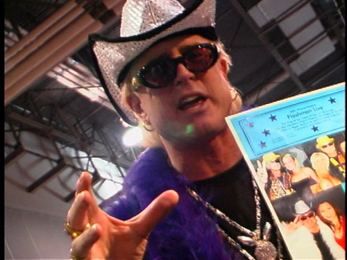 An intense man yelling at the camera at AVN, while wearing a sparkly cowboy hat.