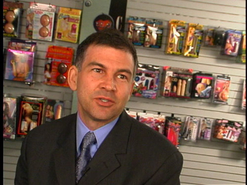 Scott Tucker, president of Topco Sales, backed by a wall of sex toys.