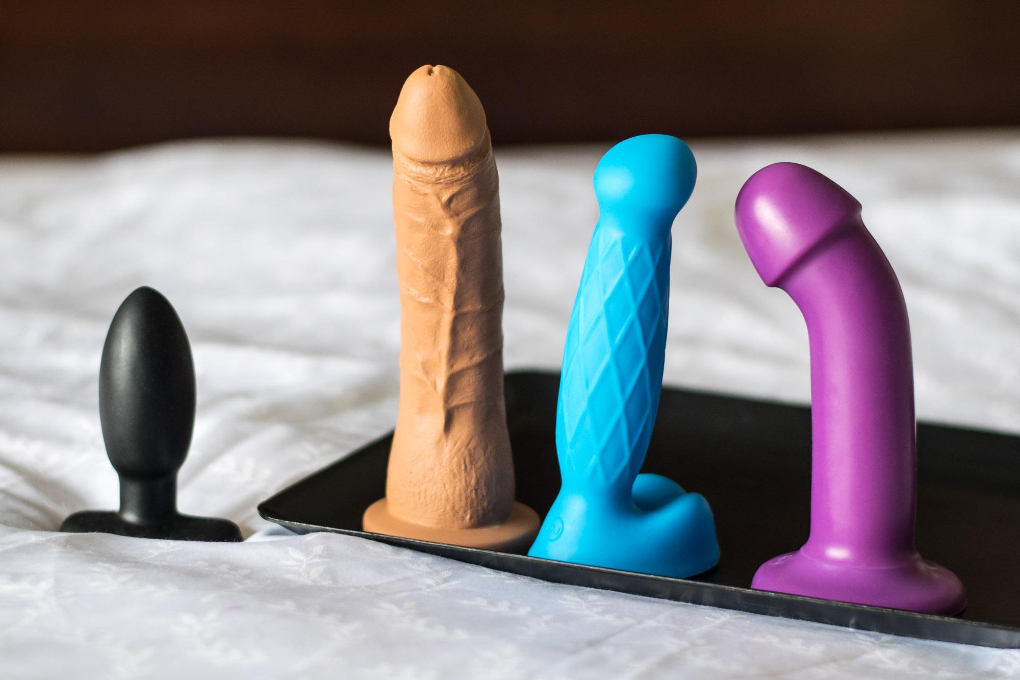 Doc Johnson TruSkyn: Tru Feel (blue), Tru Curve (purple), Tru Ride (realistic), Tru Butt Plug Smooth lying down on a black platter on top of a bed.