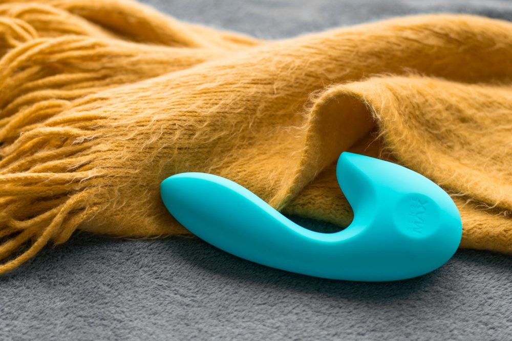 SenseMax SenseVibe rechargeable dual vibrator next to a burnt yellow fuzzy scarf.