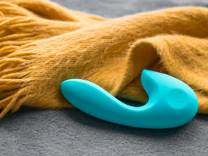 SenseMax SenseVibe rechargeable dual vibrator from above, in its case, next to a burnt yellow fuzzy scarf.