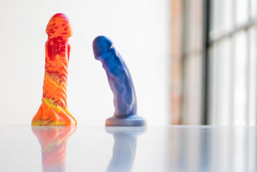 Uberrime Helios Sun God and Splendid silicone dildos standing on a table, casting a reflection.