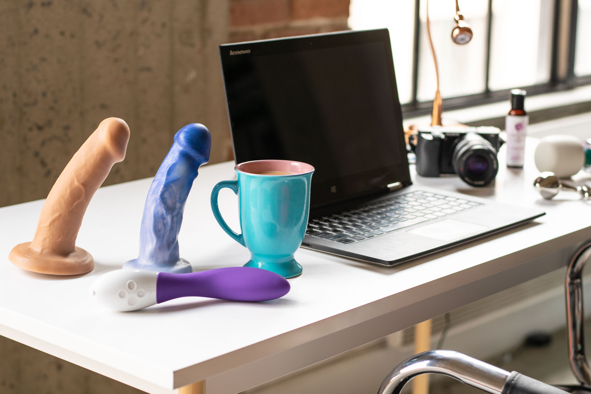A sex blogger's desk: dildos, coffee, laptop, etc.