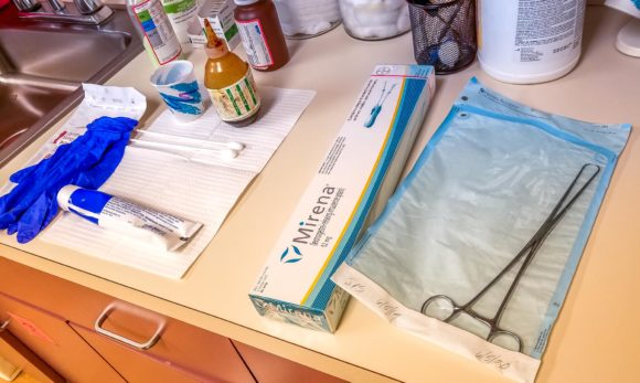 Supplies for Mirena IUD insertion laid out at the doctor's office, including forceps, lube, gloves, and the Mirena box.