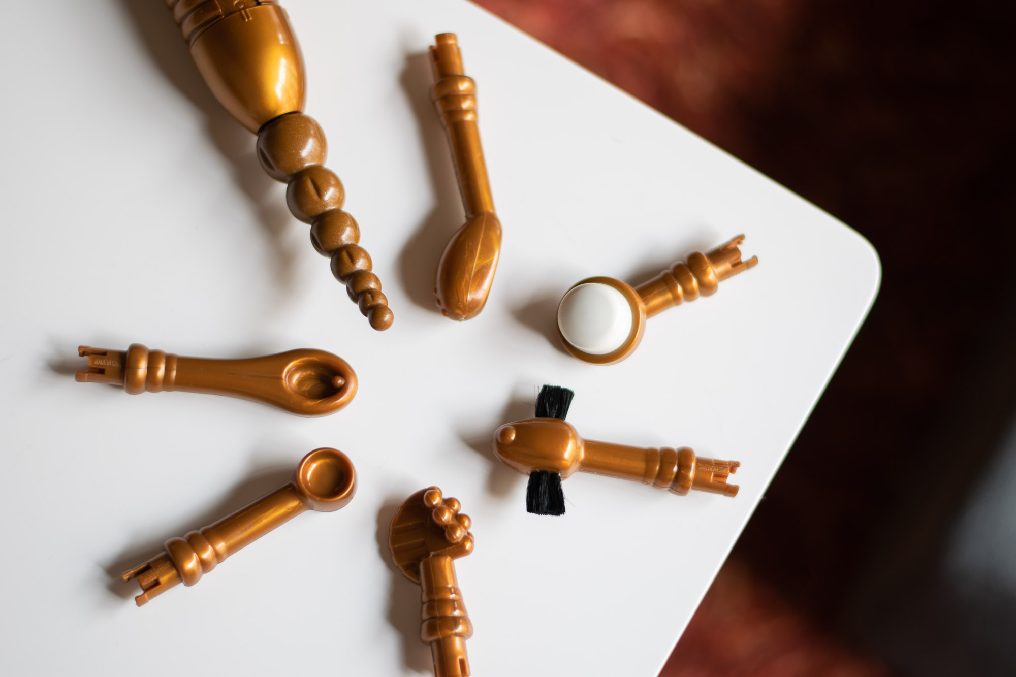 Eroscillator attachments in a circle on a white table: Seven Pearls of the Orient, G-Point, Ultra-Soft Finger Tip, French Legionnaire's Moustache, Grapes and Cockscomb, Ball and Cup, and Golden Spoon.